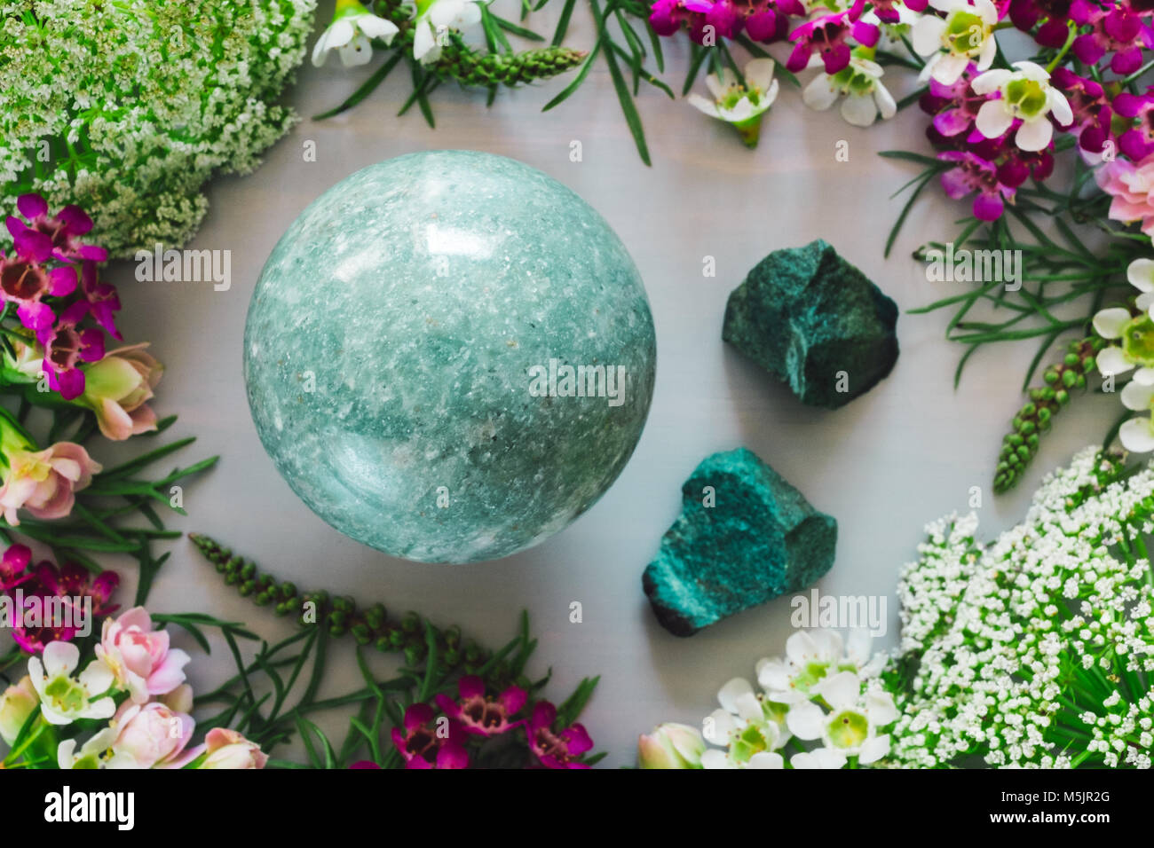 Green Aventurine Sphere with Rough Stones and Mixed Spring Flowers - Stock Image