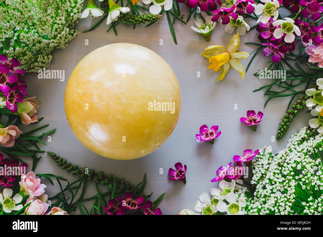 Yellow Aventurine Sphere with Mixed Spring Flowers - Stock Image