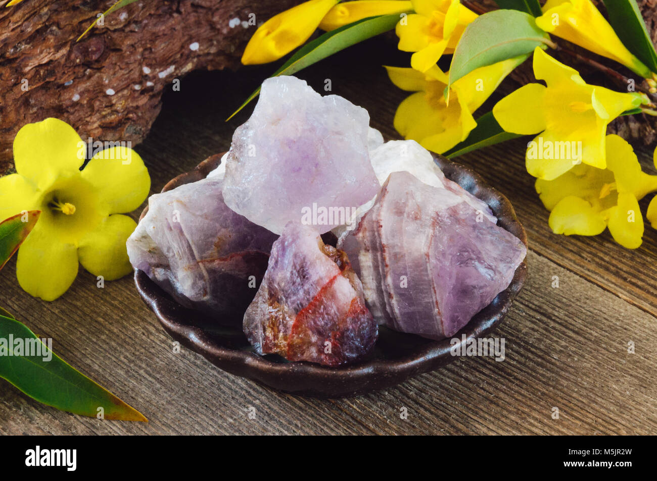 Ceramic Bowl of Rough Amethyst on Rustic Background - Stock Image