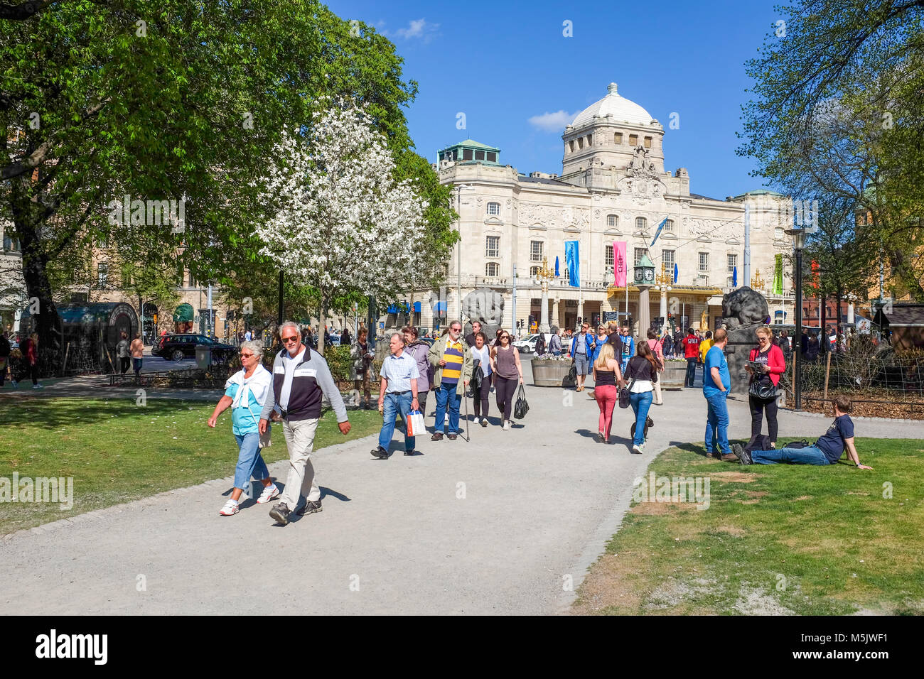 People stroll in Berzelii park during spring in Stockholm. The Royal Dramatic Theater in the background was built - Stock Image