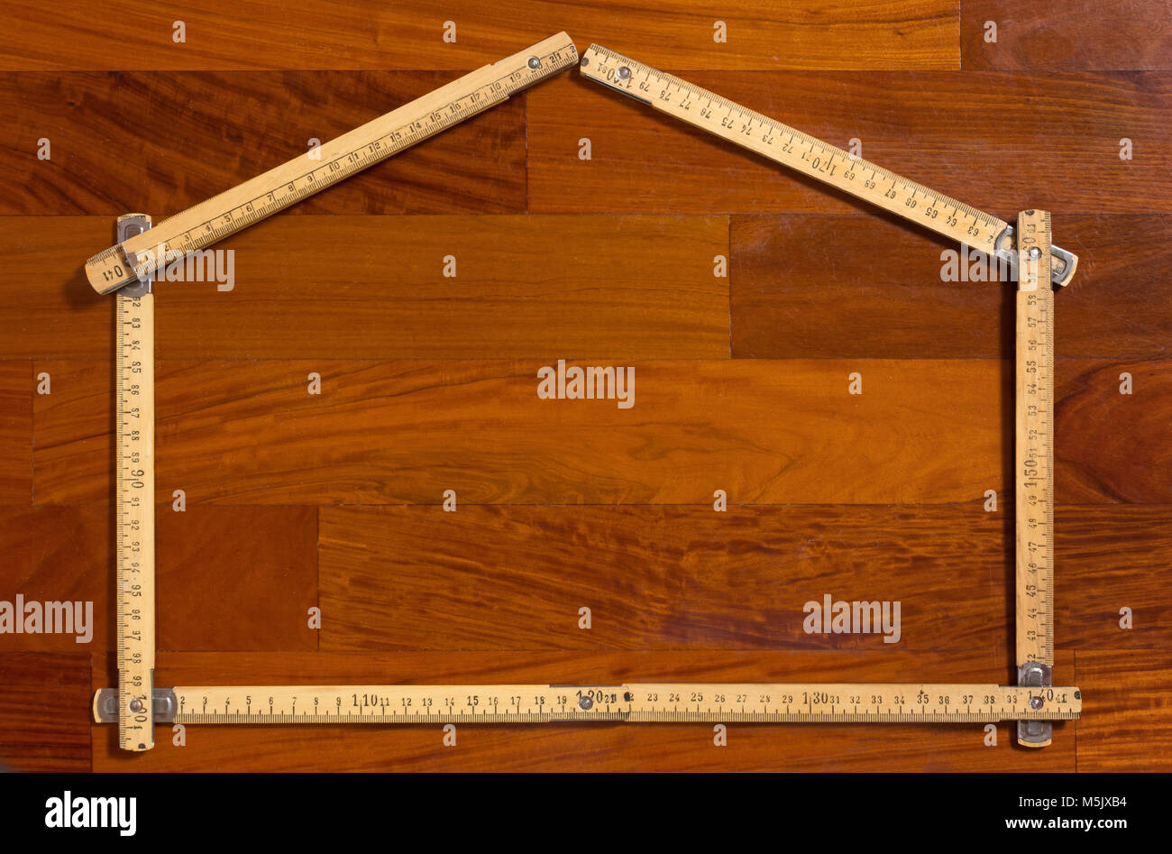 Measuring stick folded in the shape of a house on a wooden background - Stock Image