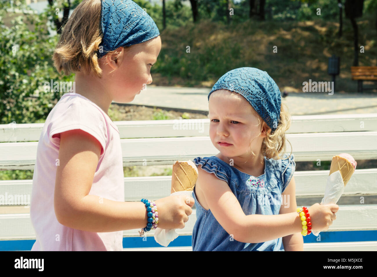 The little girl doesn't want to change ice cream with his sister, selective focus. - Stock Image