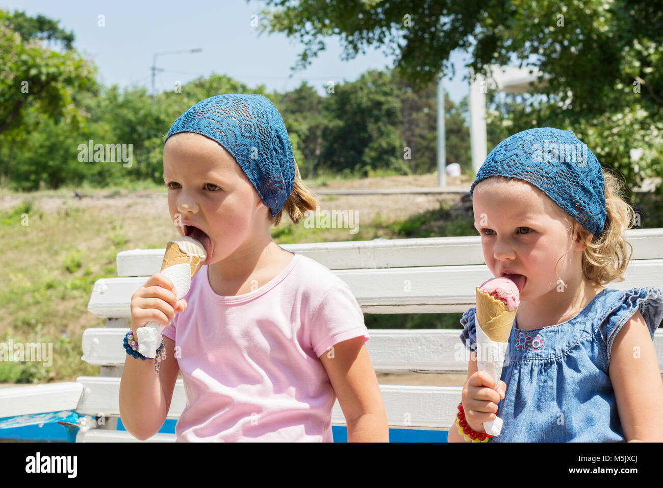 Little cute girls (sisters) eat ice cream, selective focus. - Stock Image