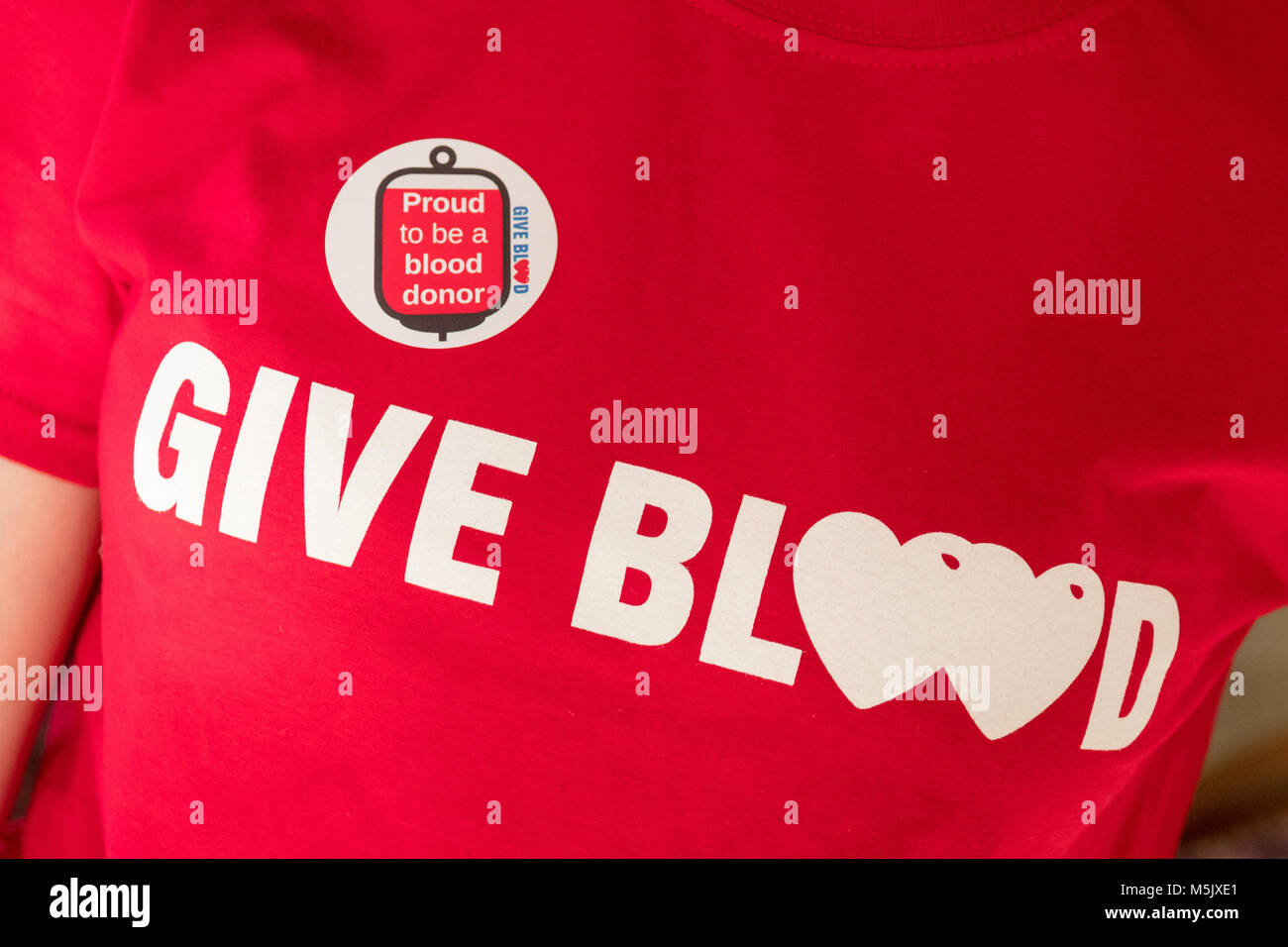 give blood t shirt and proud to be a blood donor sticker - UK - Stock Image