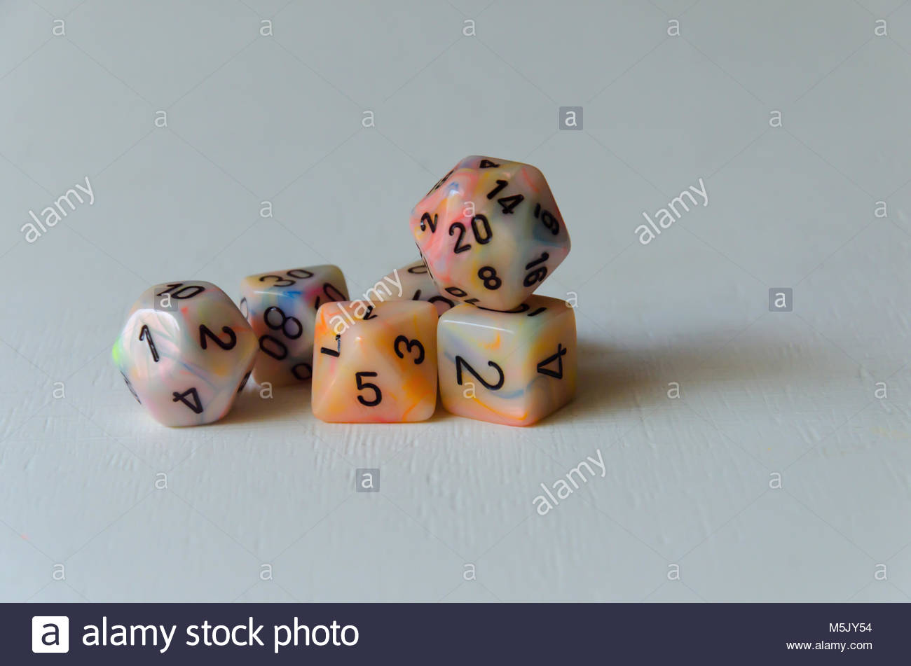 Multi sided numbered dice on white background - Stock Image