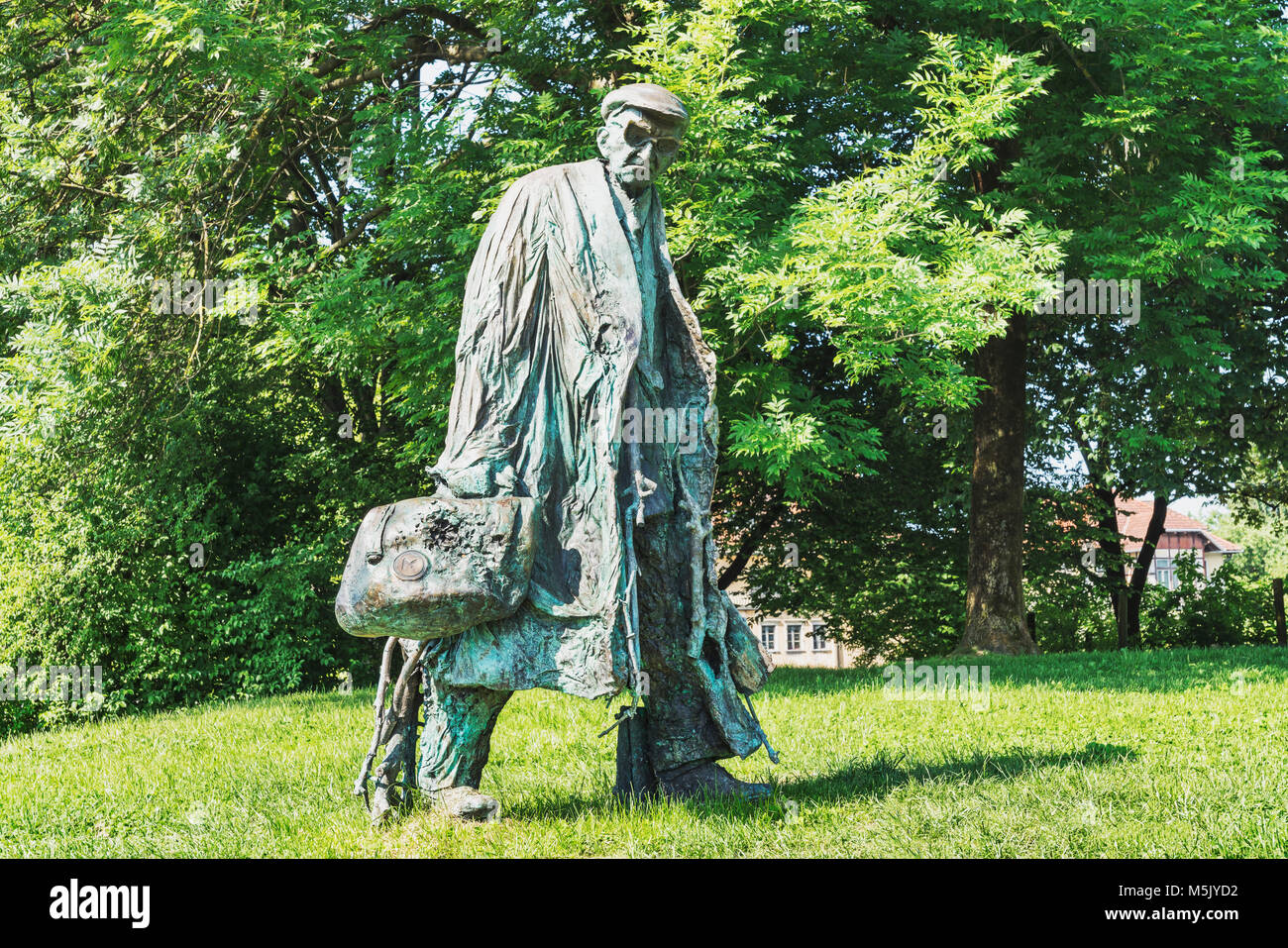 The bronze statue of a tall man with a bag, glasses and cap is located in the Tivoli Park Ljubljana, Slovenia, Europe - Stock Image