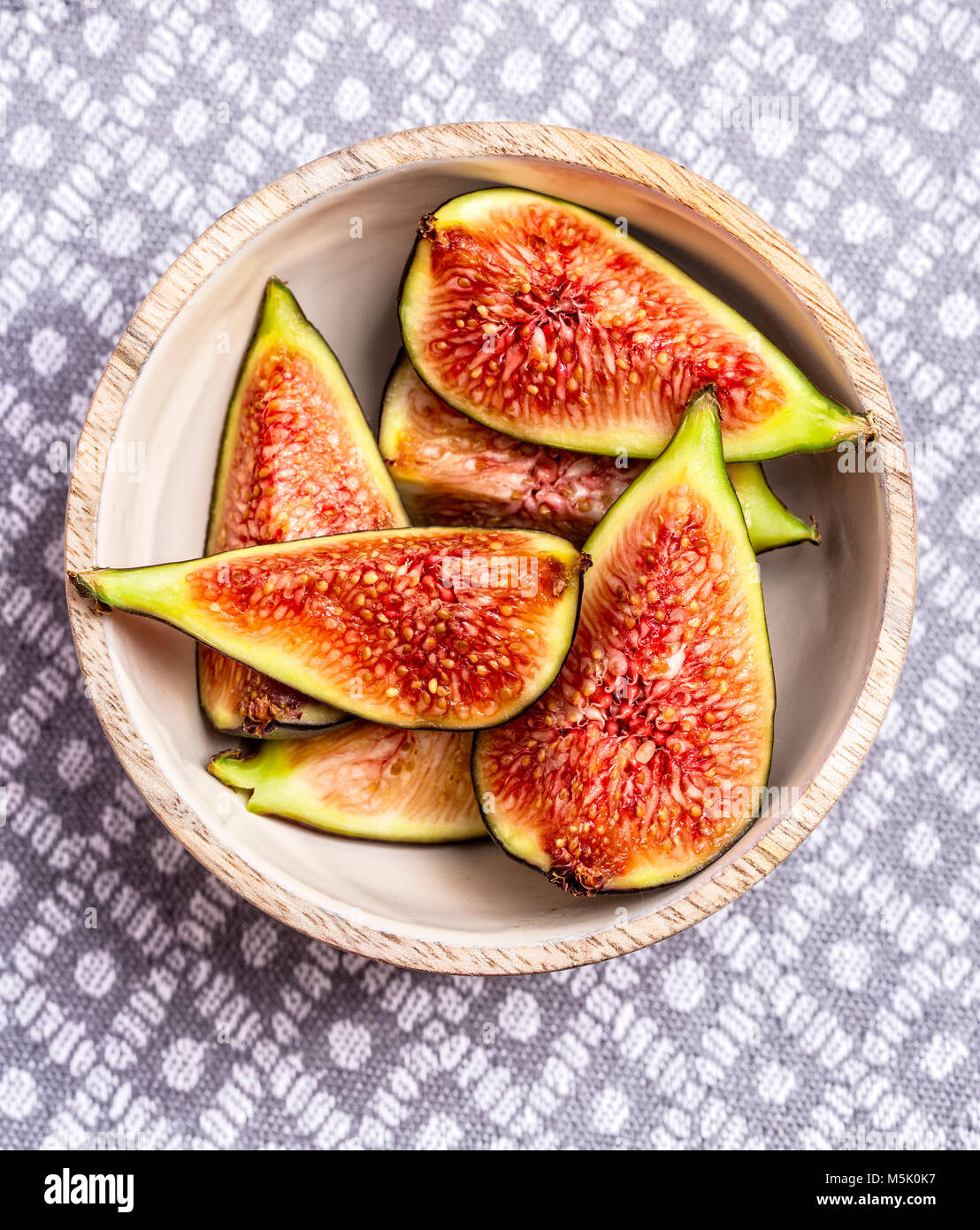 Fresh Figs on a wooden bowl on a light grey textured background Stock Photo