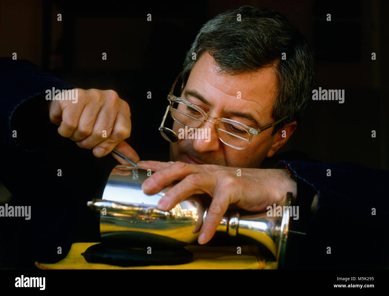 Engraver working on silver trophy - Stock Image