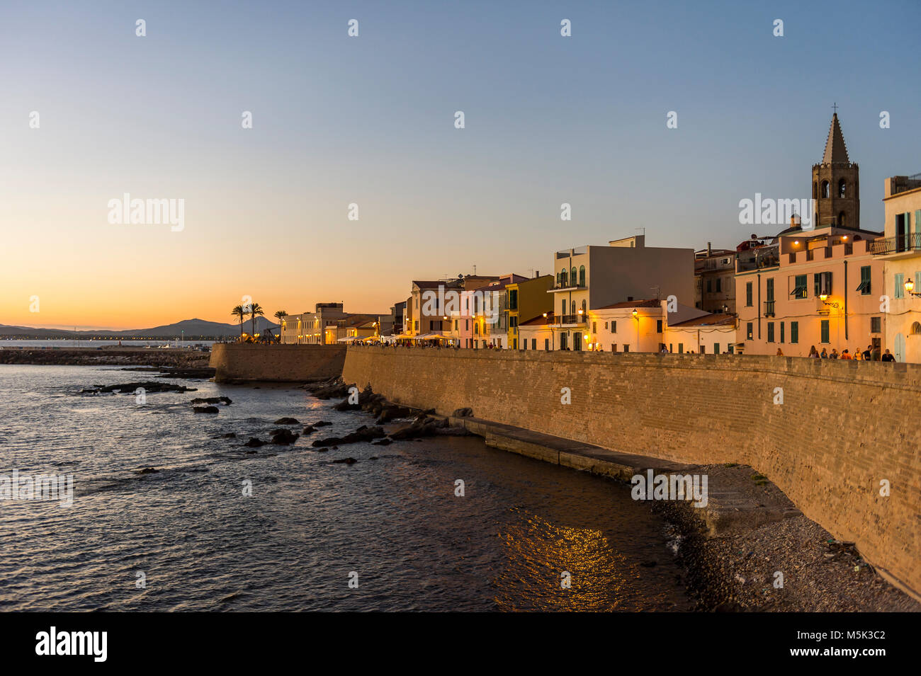 Waterfront in the coastal town of Alghero after sunset, Sardinia, Italy Stock Photo