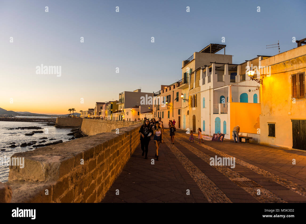 Waterfront in the coastal town of Alghero after sunset, Sardinia, Italy - Stock Image