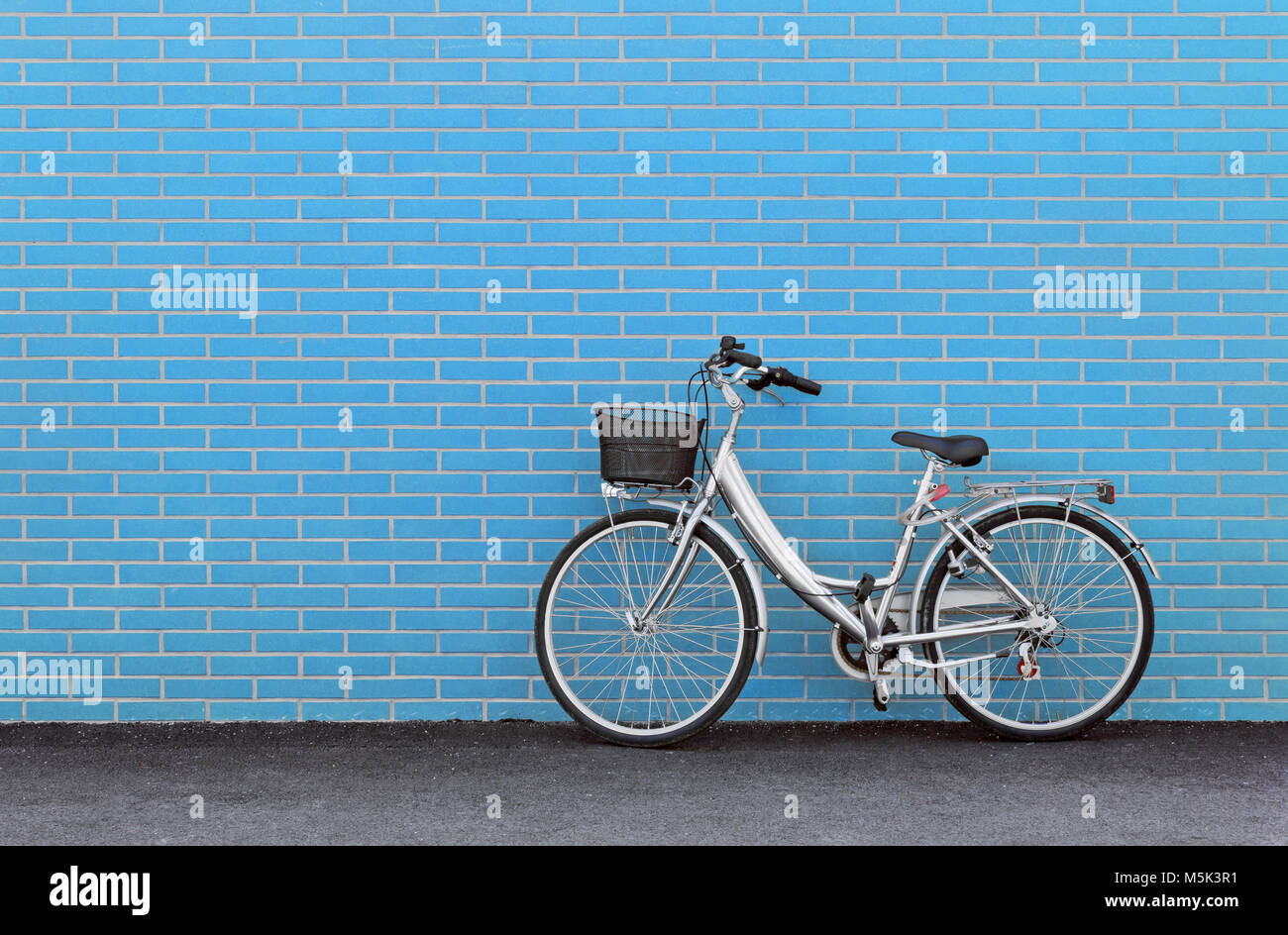 Women's bicycle against a turquoise brick wall - Stock Image