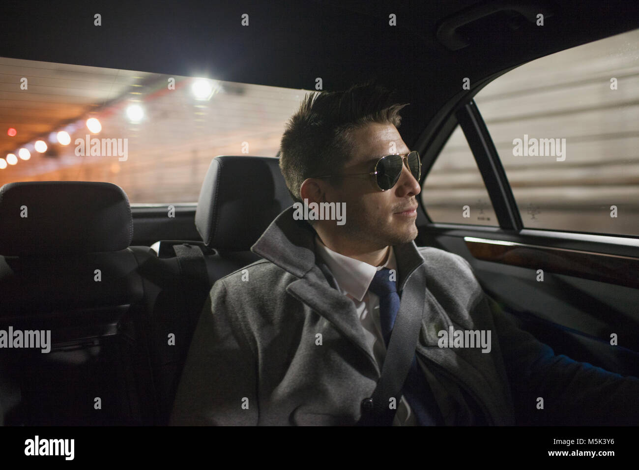 Young business man looking looking out the window sitting in car service limousine - Stock Image