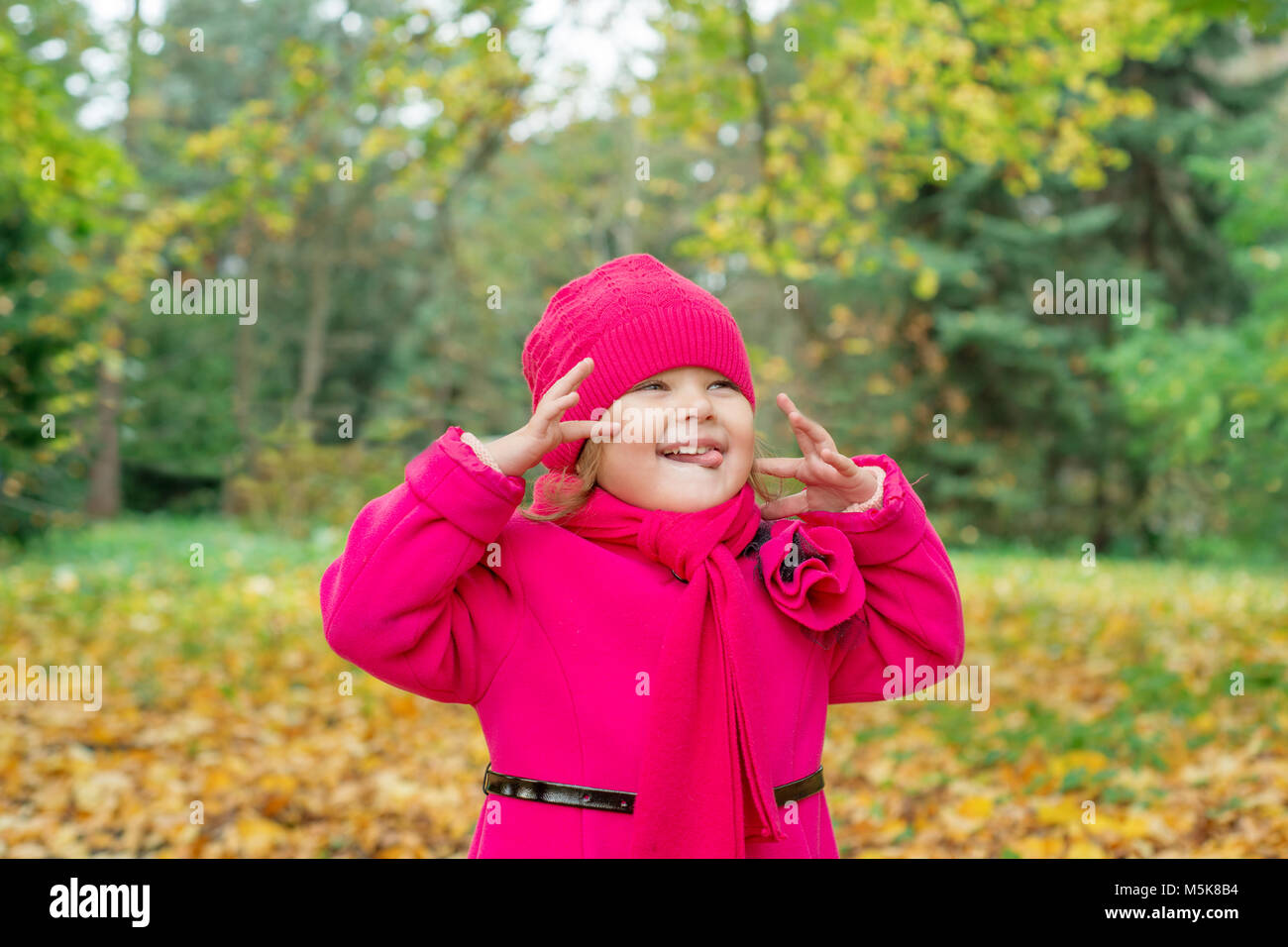 Girl in pink coat monkeys and shows tongue in autumn park - Stock Image