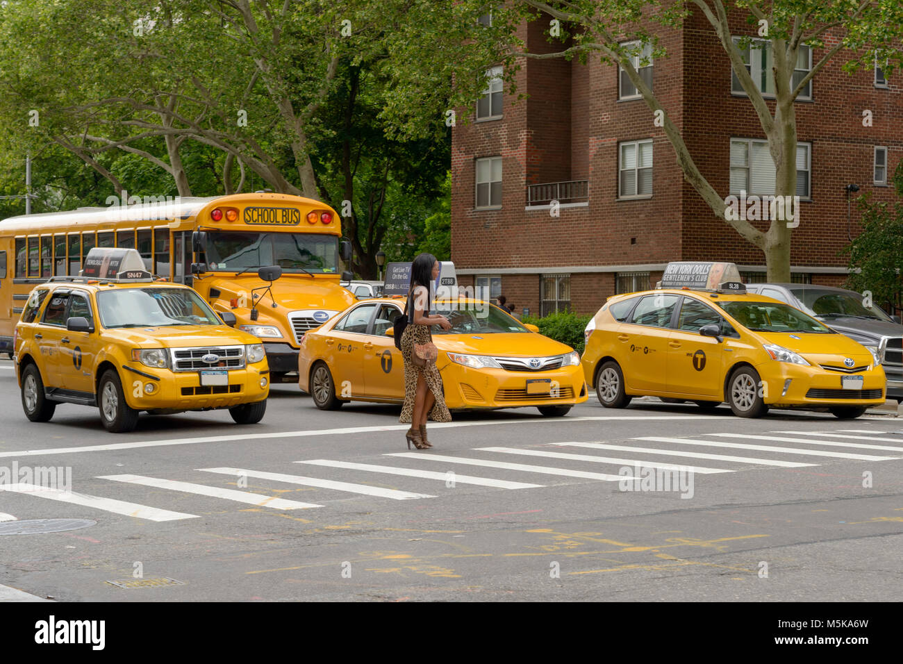 New York City, USA - June 08, 2015: New York yellow taxi cab stop at pedestrians traffic lights crossing the street Stock Photo