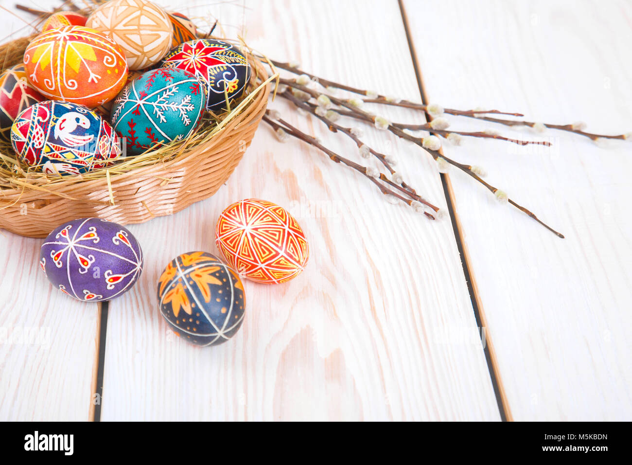 Easter eggs in a basket on a white plank background. Symbol of Christian holidays. - Stock Image