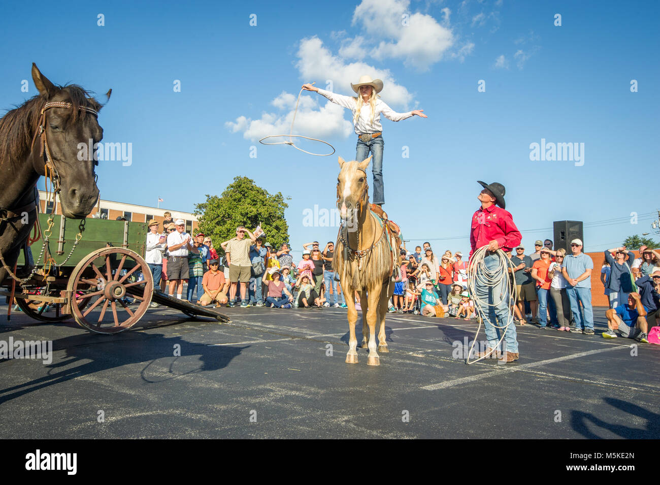 Man in cowboy hat watches young girl standing on top of horse and  preforming rope trick