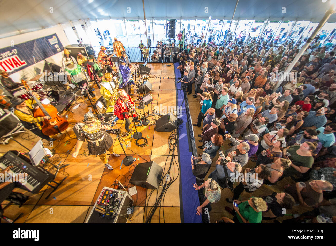 The cosmic musical group Sun Ra Arkestra preforming together on stage with crowd tentatively watching at National - Stock Image