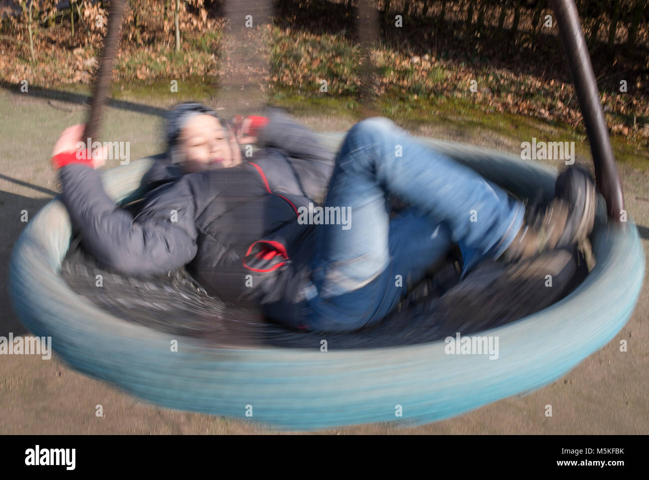 Boy swinging and whirling on a round swing, playground, blurred by motion and speed. - Stock Image