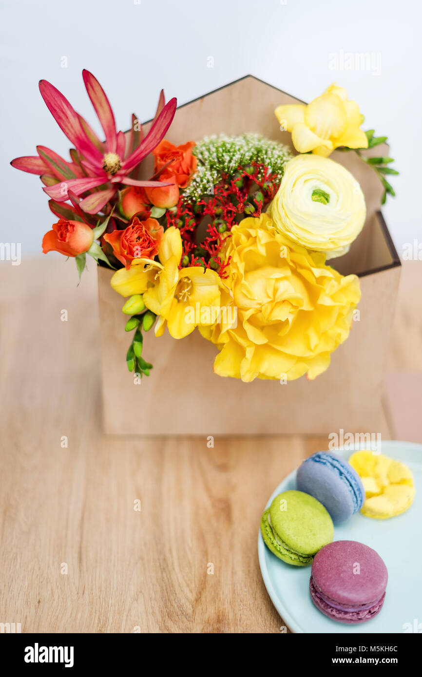 Giftbox with flowers and sweets. Macaroons and spring bouquet in wooden box. - Stock Image