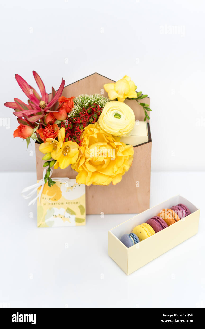 Giftbox with flowers and sweets. Macaroons and spring bouquet in wooden box on white background. - Stock Image