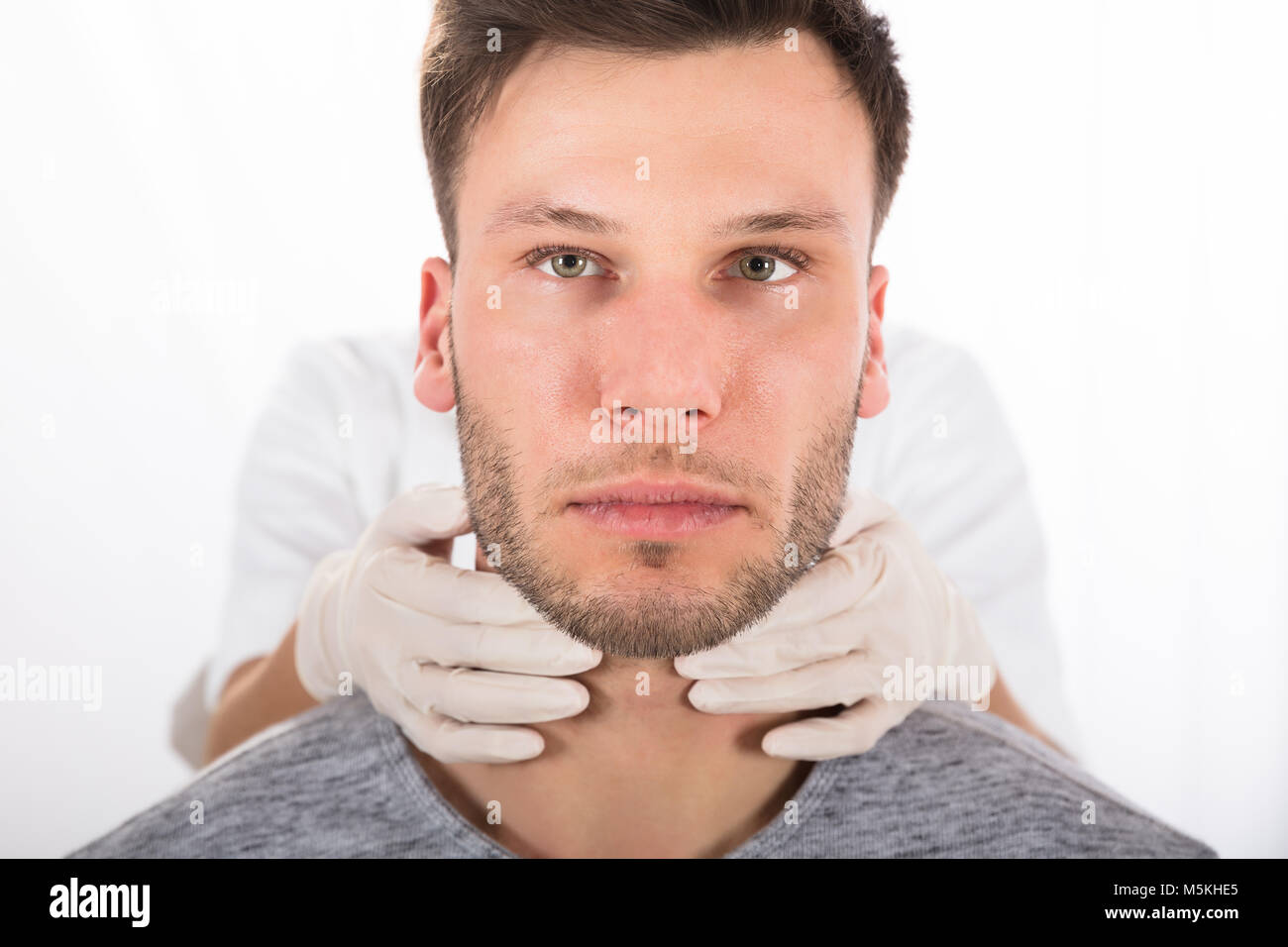 Doctor Performing Physical Exam Palpation Of The Thyroid Gland - Stock Image
