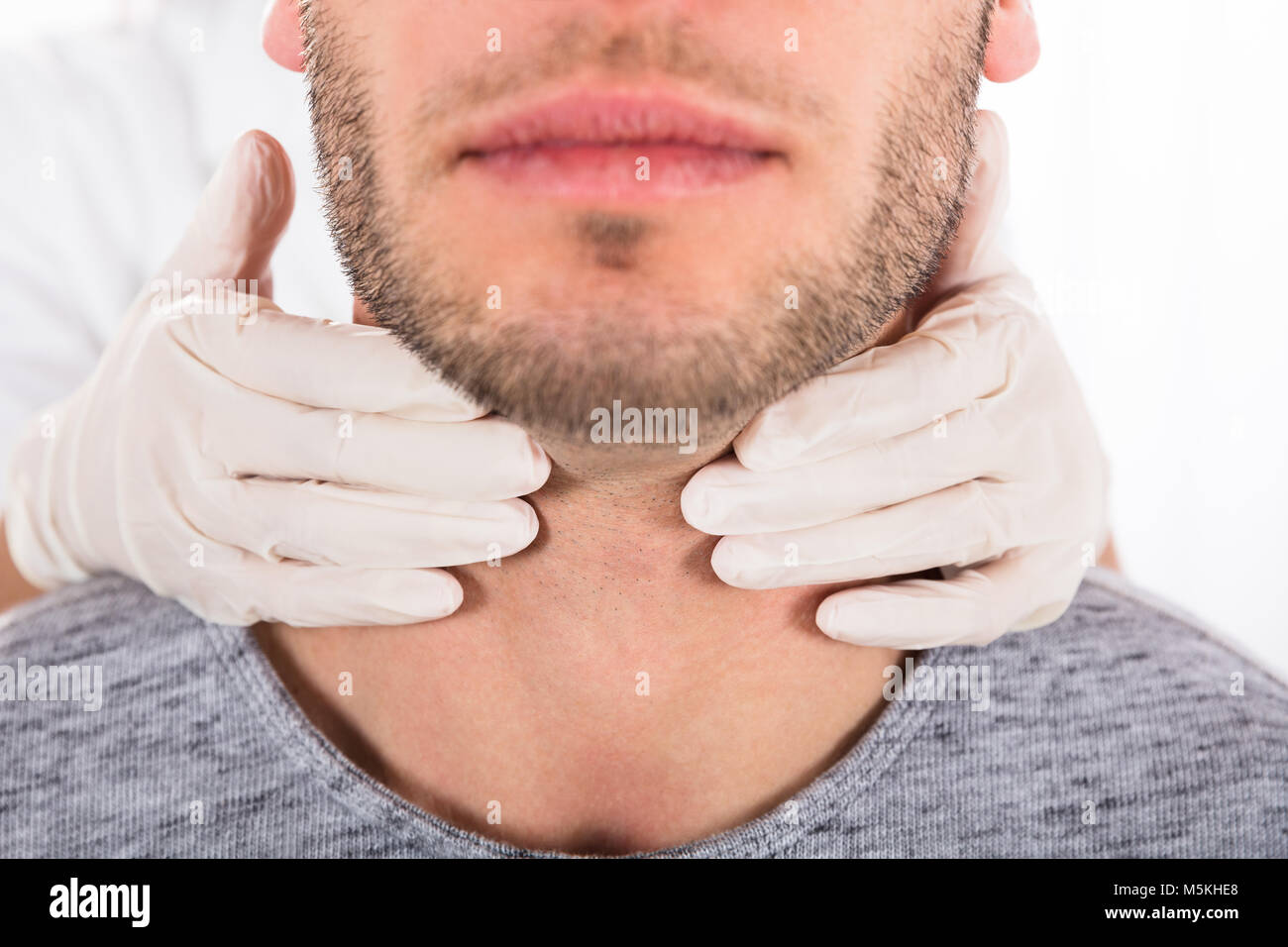Doctor Performing Physical Exam Palpation Of The Thyroid Gland Stock Photo