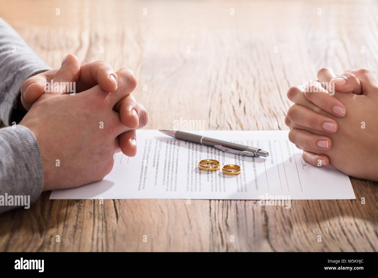 Hands Of Wife And Husband On Divorce Document With Wedding Ring In The Center - Stock Image