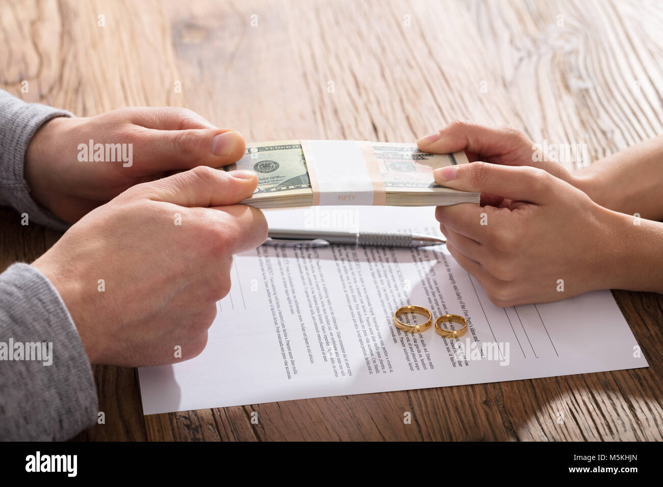 Couple's Fighting For Money Over The Divorce Agreement With Gold Wedding Rings - Stock Image