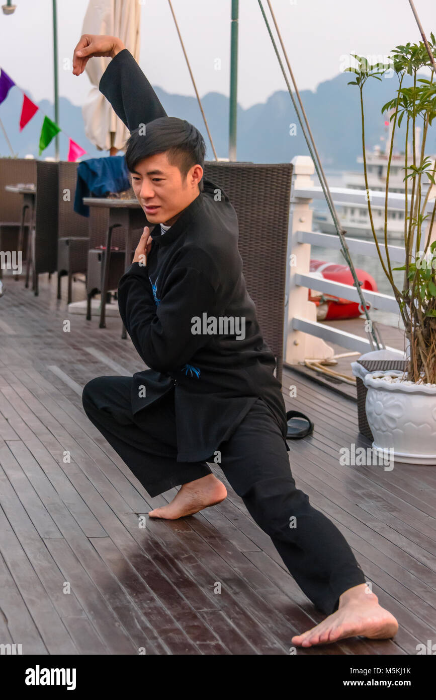 A Vietnamese man leads a group of tourists in a Tai Chi class at sunrise on the upper deck of a cruise ship in Halong Stock Photo