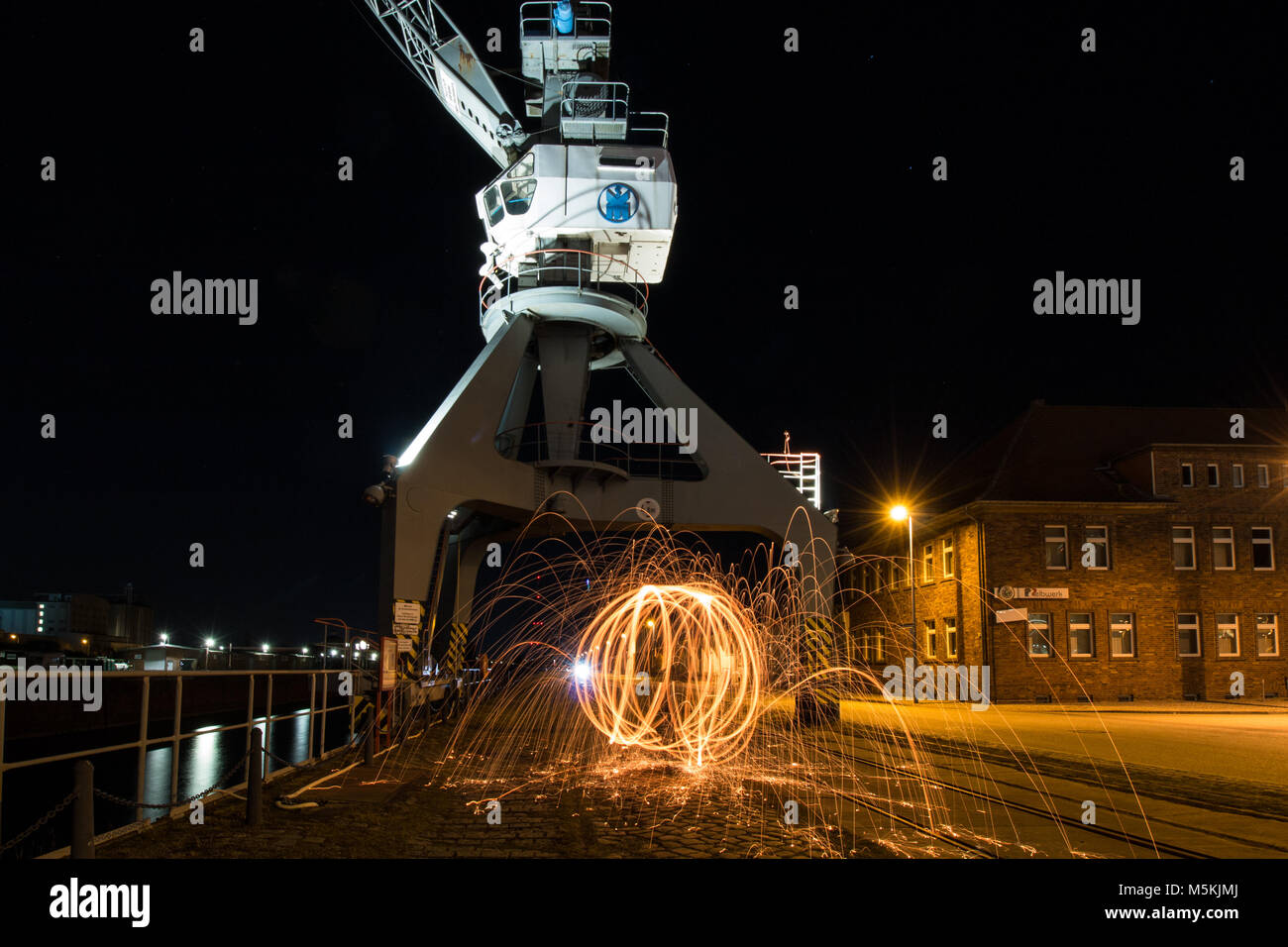 Old loading crane with fireball. Steel wool. At an old dock. Stock Photo