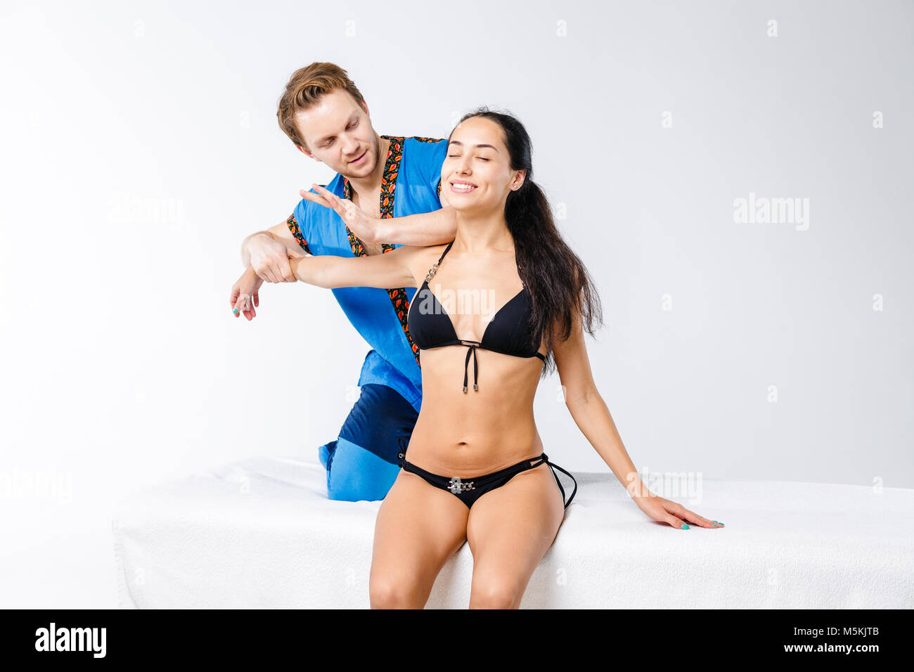 Theme massage and body care. Young doctor masseur in working suit makes massage to relax and strengthen the muscles - Stock Image