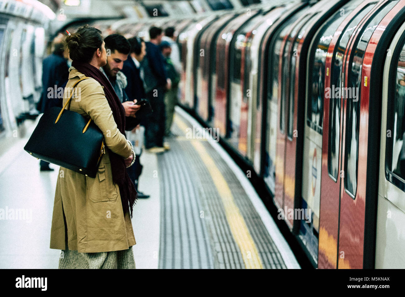 Commuters wait for the Central Line underground train in Bank Station, London - Stock Image
