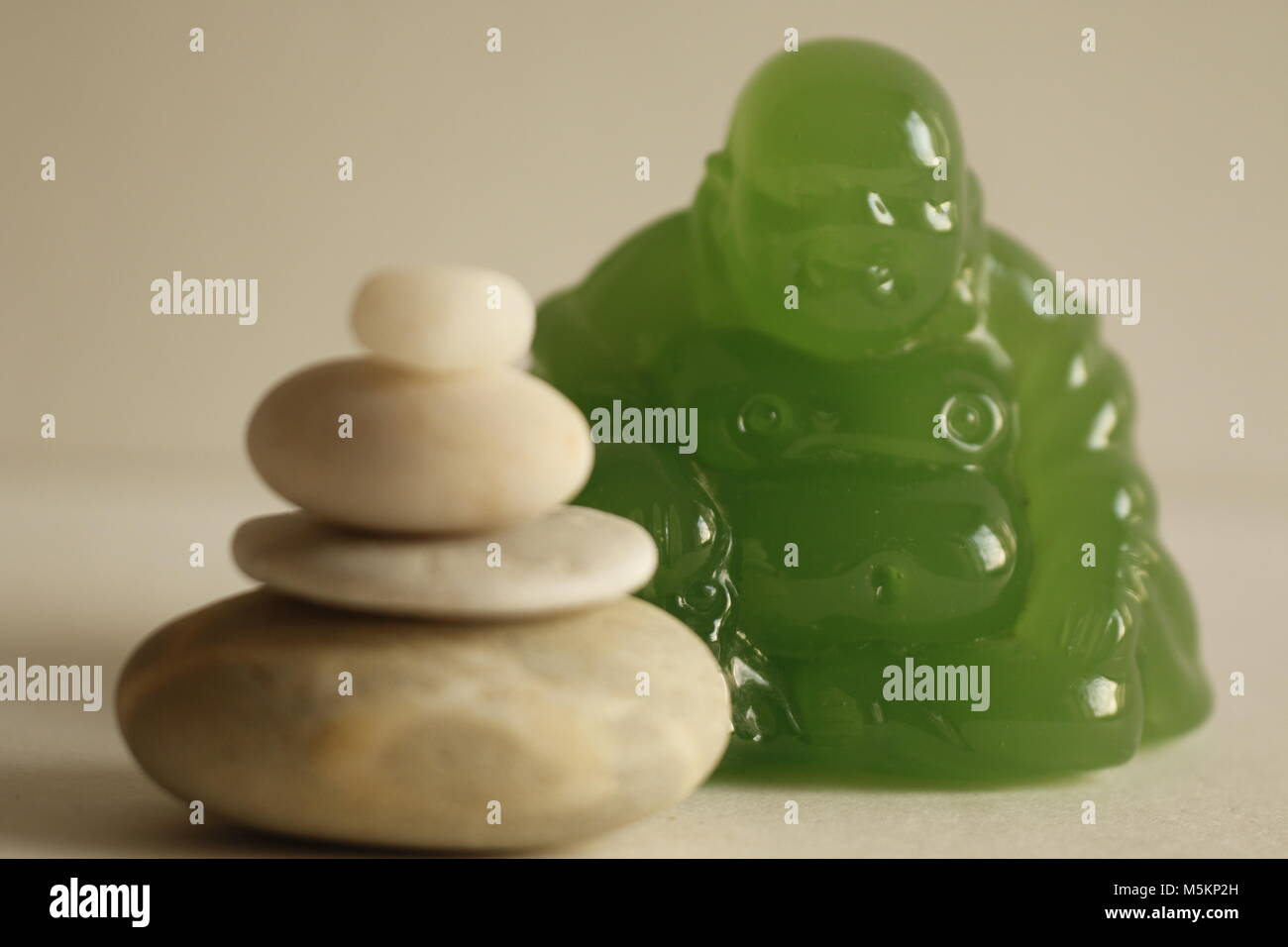 White pebble stones and a green Buddha - Stock Image