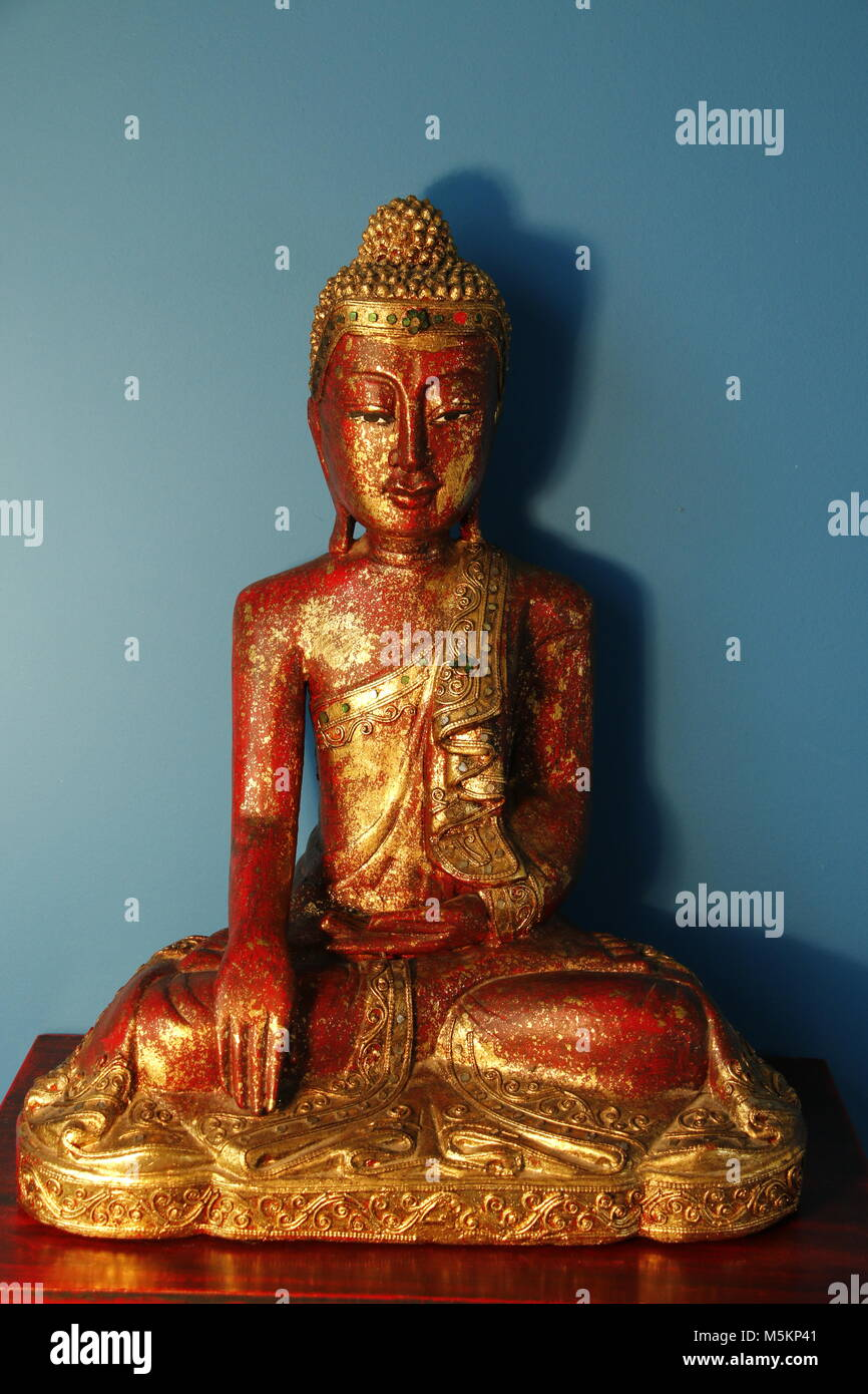 Statue of a red golden buddha - Stock Image