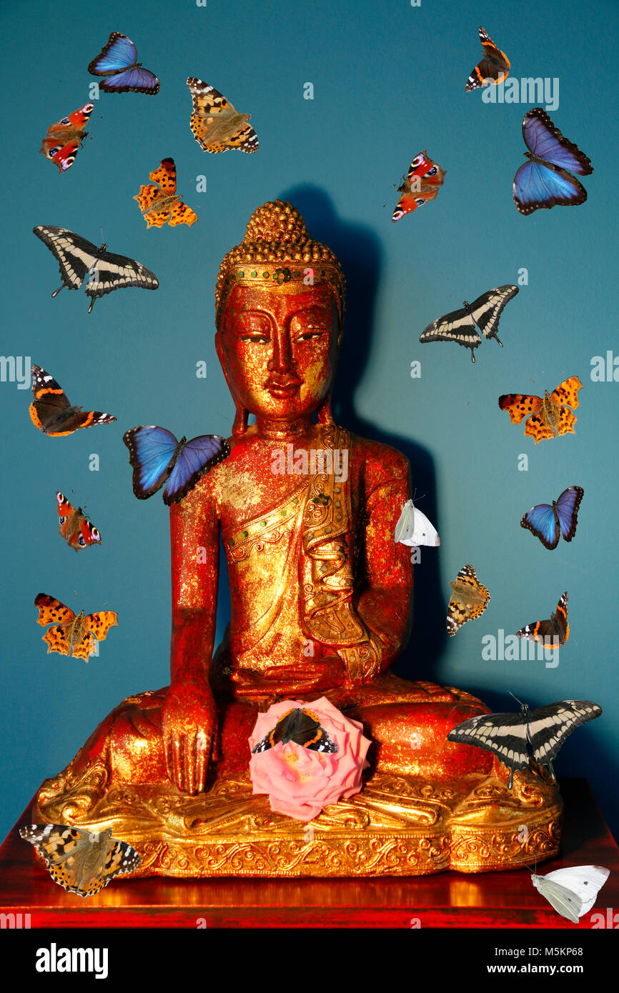 Red golden Buddha surrounded by butterflies - Stock Image