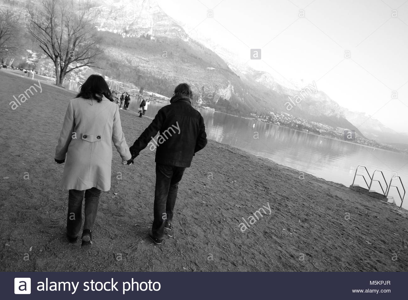 Black and white view of people enjoying  Annecy lake banks on a cold winter morning, Savoy, France - Stock Image