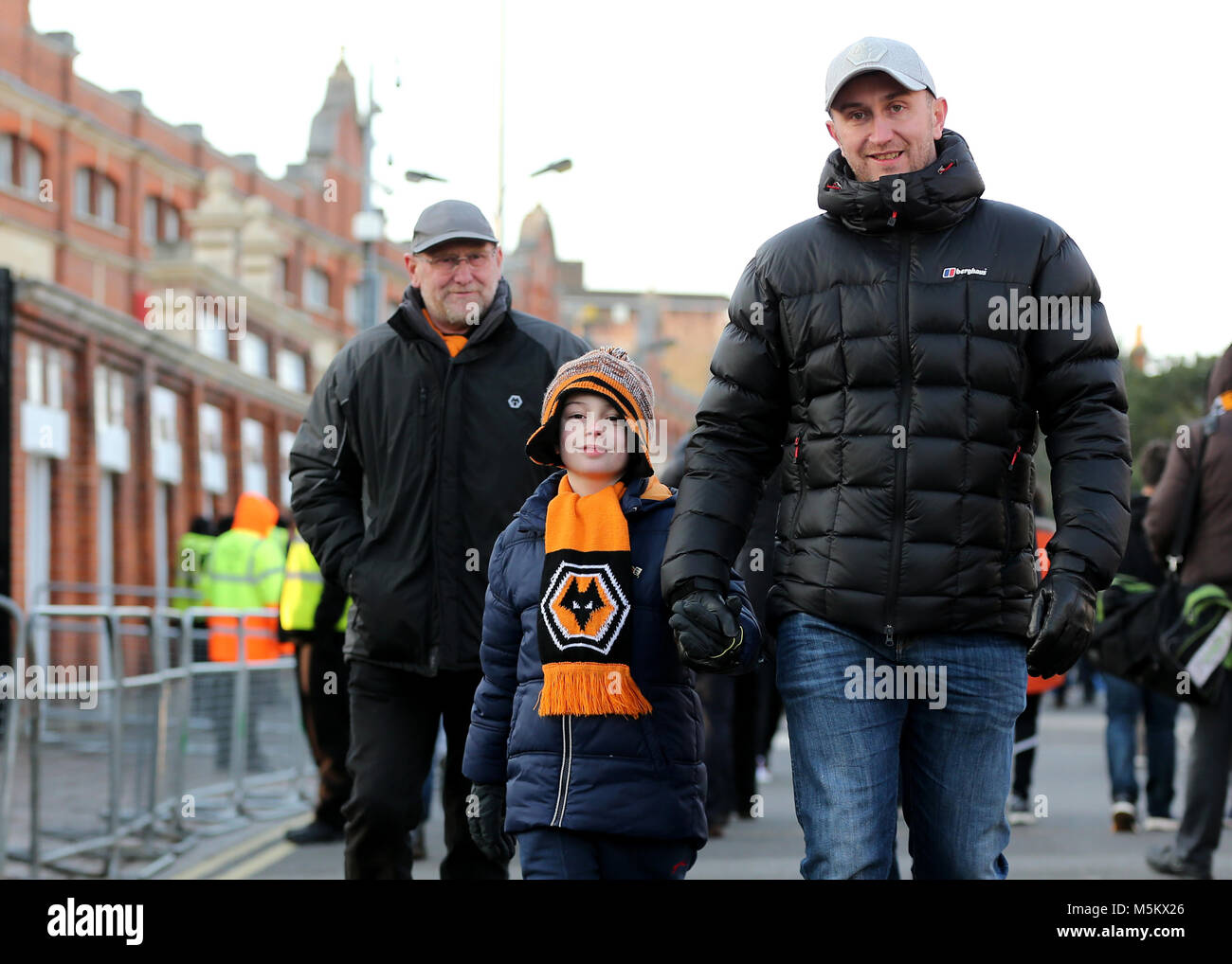 Wolves fans make their way to the ground before the Championship match at Craven Cottage, London. - Stock Image