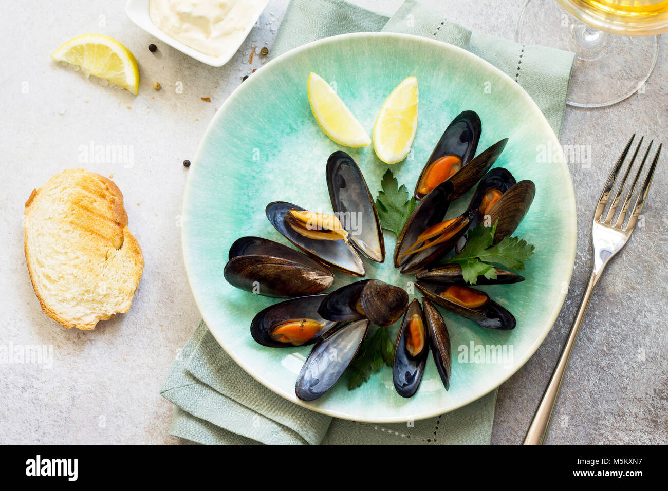 Still life, restaurant dinner.  boiled in white wine sauce with a glass of white wine, white bread toast, garlic - Stock Image