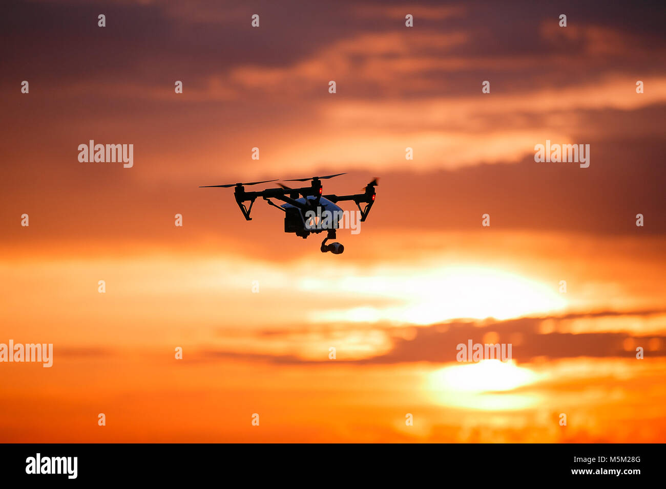 quadrocopter drone with remote control. Dark silhouette against colorfull sunset. Soft focus. Toned image - Stock Image
