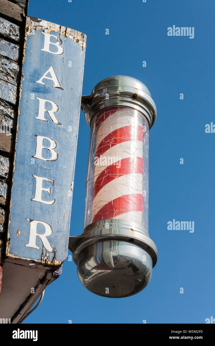 Traditional red and white barbers pole outside men's hairdressers - Stock Image