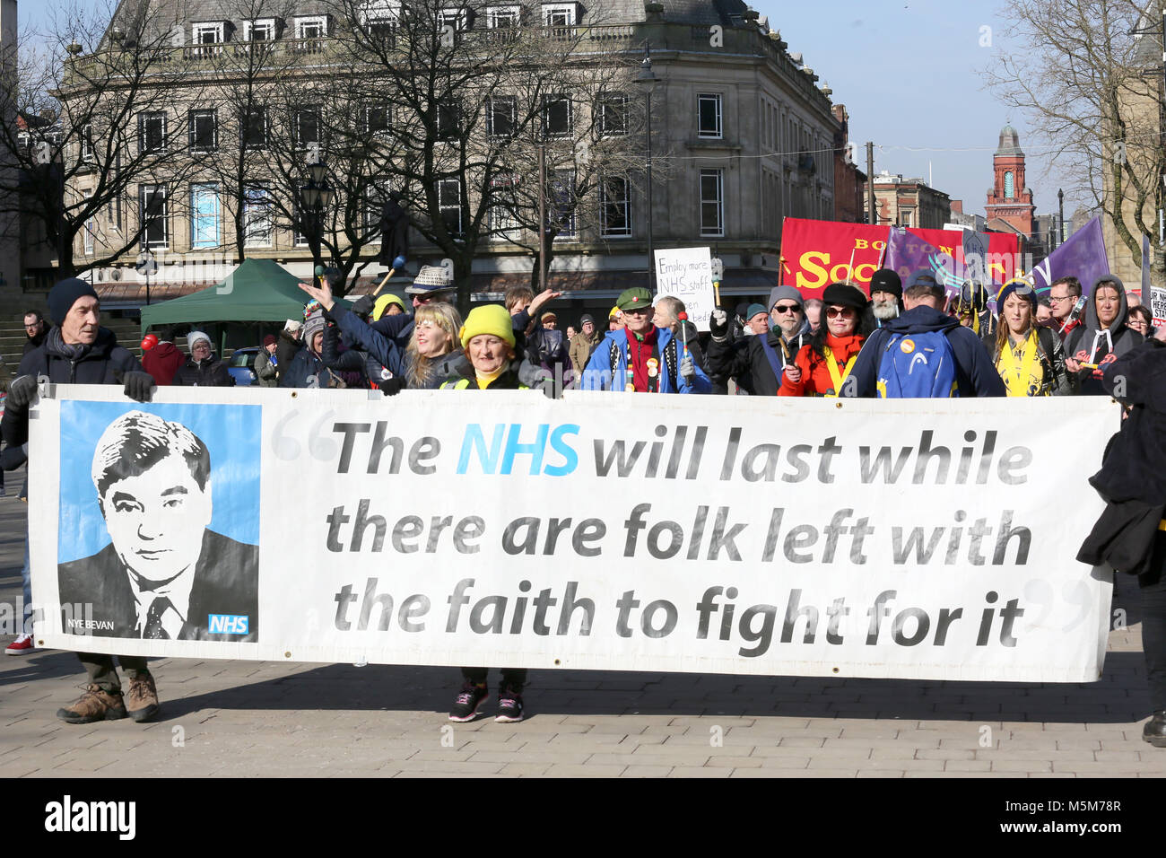 A march to defend the NHS is led with a banner which reads a quote by Nye Bevan reading 'The NHS will last while - Stock Image