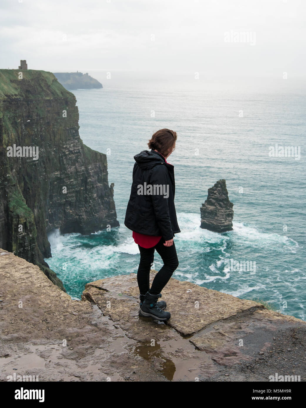 Standing on the edge of the mighty Cliffs of Moher - Stock Image