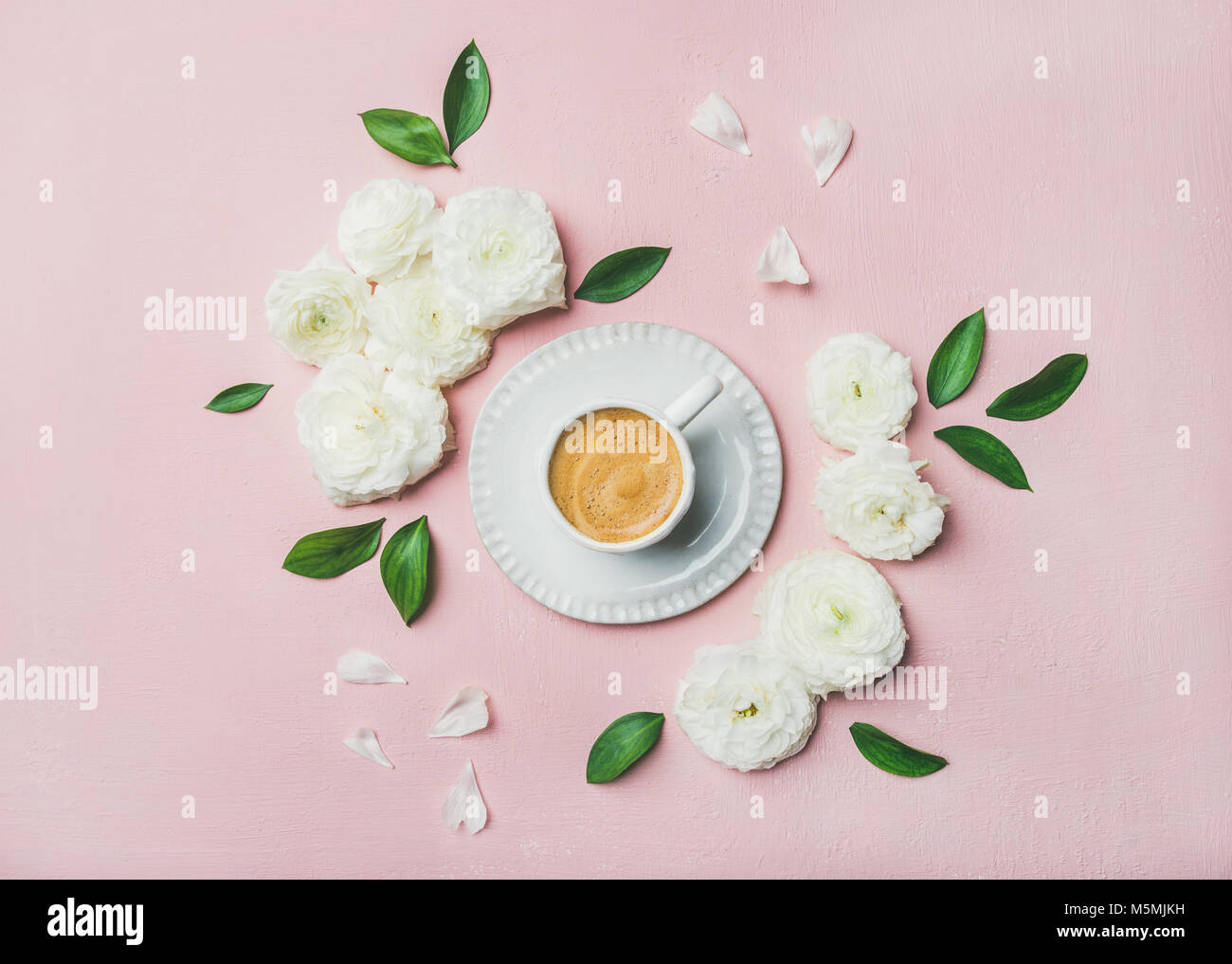 Cup of coffee surrounded with white ranunculus flowers - Stock Image