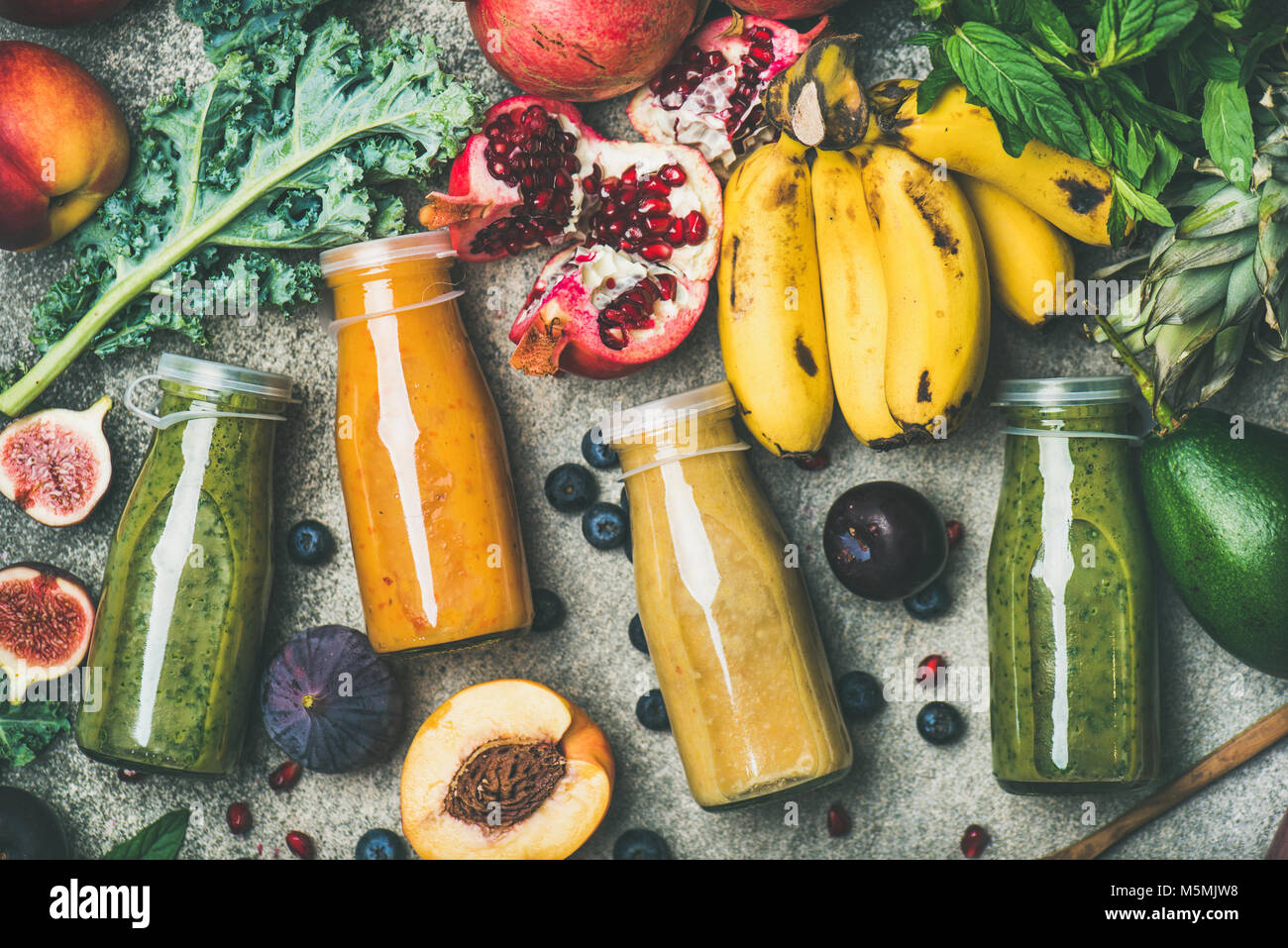 Colorful smoothies in bottles with fresh tropical fruit and vegetables - Stock Image