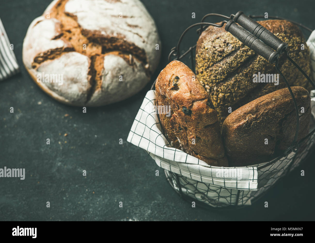 Various bread loaves over black background, copy space - Stock Image