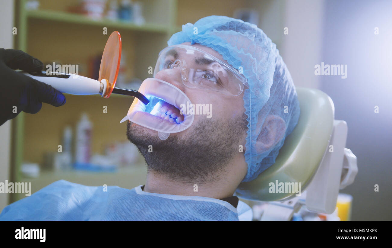 Doctor and patient with retractor in the dental office, cleaning with ultraviolet light and orange protective screen - Stock Image