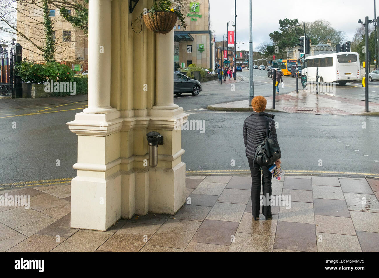 A woman standing under the portico of the Angel Hotel in Cardiff City Centre in Wales. - Stock Image