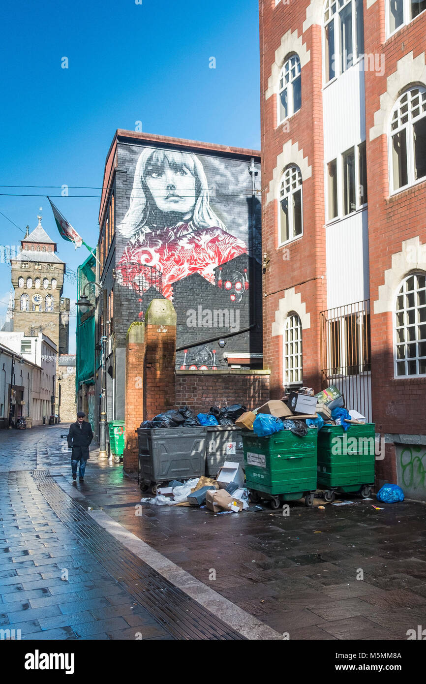 Overflowing rubbish garbage bins in a back street in Cardiff City centre. - Stock Image