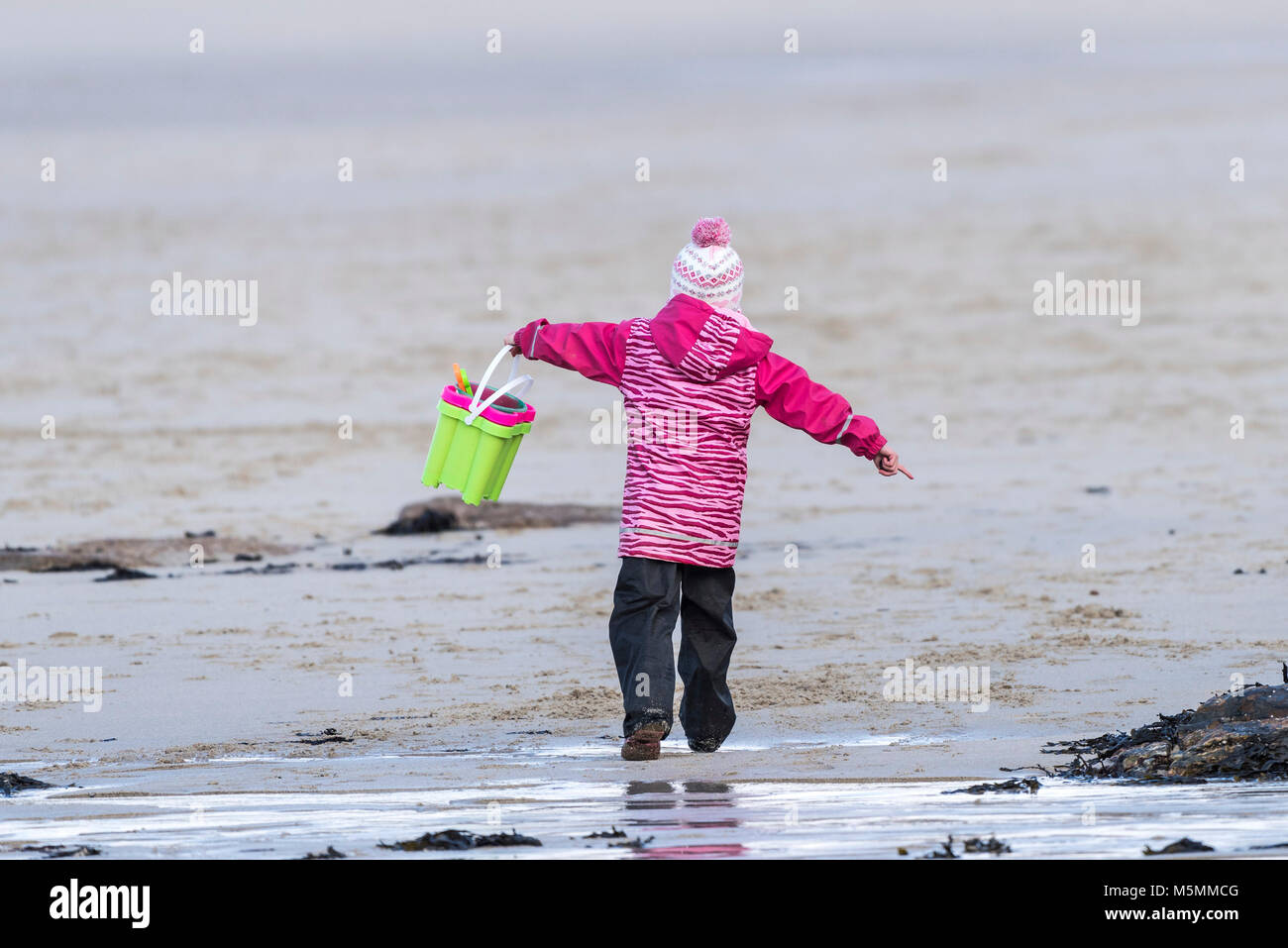 A young child playing and running around on a beach. - Stock Image