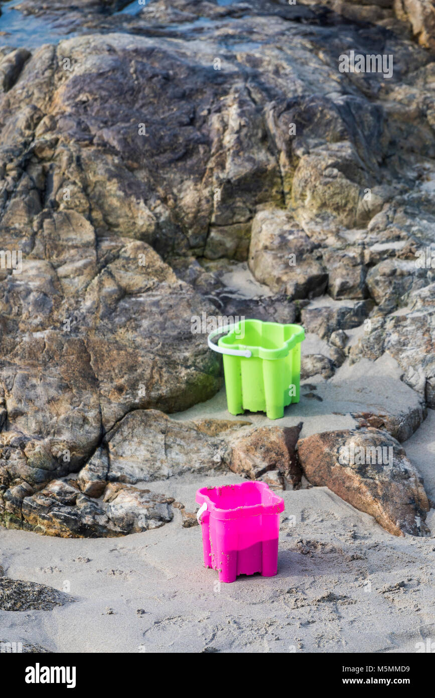 Two brightly coloured plastic buckets left on the beach at Sennen Cove in Cornwall. - Stock Image